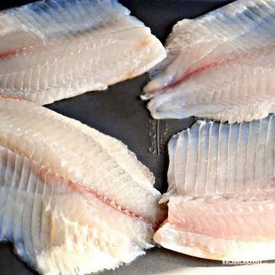 Выкладываем кусочки филе нашей рыбы на противень либо в посудку для выпекания. Обильно смазываем рыбу нашим чесночно-лимонным соусом.