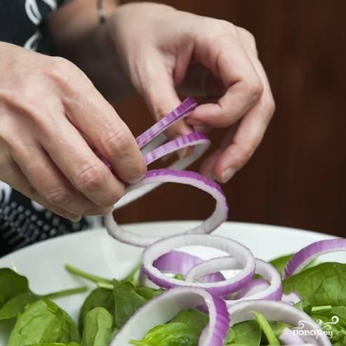 3. Очистите луковицу и нарежьте тонкими кольцами. Кольца разделите и добавьте в миску к шпинату.