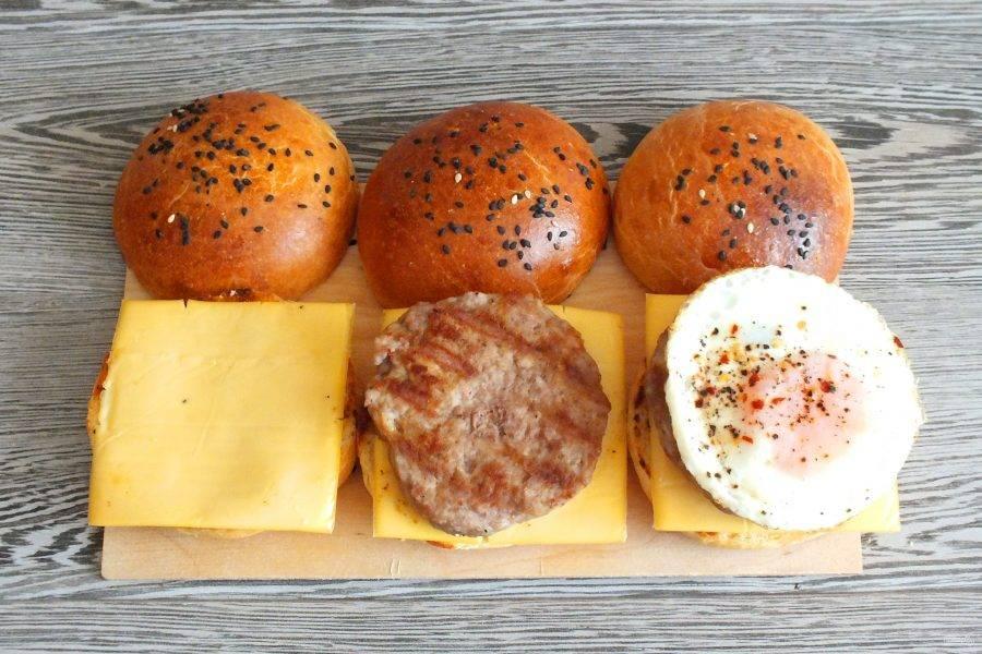 Соберите макмаффины. На половинку булочки выложите пластинку сыра, котлету, яйцо.