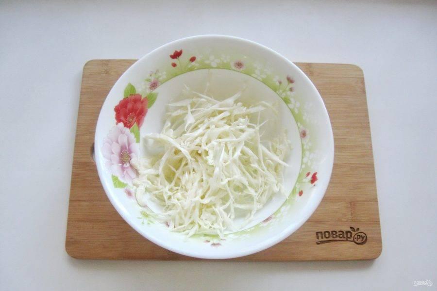 Белокочанную капусту нарежьте тонкой соломкой и выложите в салатник.