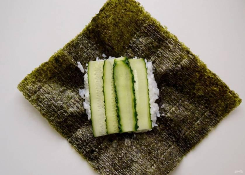 Сверху положите ломтики огурца. Затем шпинат. Сверху пластинки тофу. Если что-то выходит за границы риса, то лишнее можно отрезать.