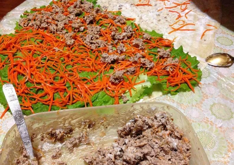 Раскладываем на столе лаваш, смазываем его слоем майонеза. Сверху, на одну половину лаваша, выкладываем промытые листья салата и корейскую морковь. Далее выкладываем куриную печень.