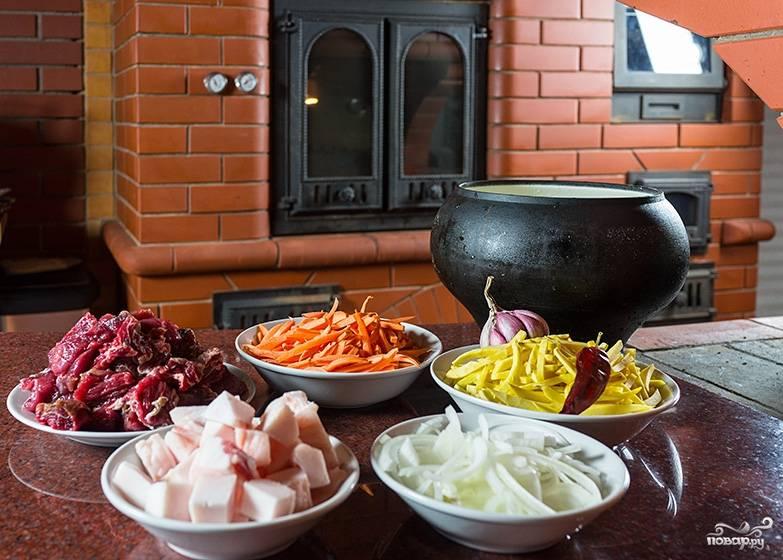 Подготовьте ингредиенты. Мясо порежьте кубиками небольшими. Соломкой порежьте морковку, а лук - полукольцами. Сало порежьте кубиками.