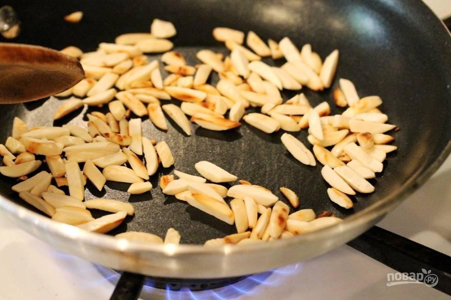 Подогрейте сухую сковороду. Обжарьте на ней очищенный и нарезанный миндаль до золотистого цвета. Это займёт у вас 3-4 минуты. Затем уберите его остывать.