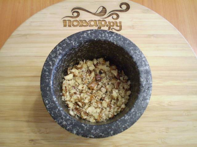 Орехи освободите от кожуры и растолките в ступке.