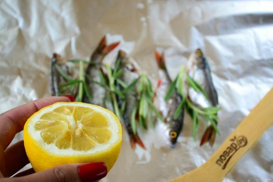 Между рыбкой положите листики розмарина, сбрызните лимонный соком.