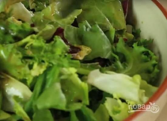 Поливаем заправкой листья салата, перемешиваем.