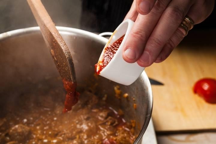 Через 1,5 часов кладем в кастрюлю томатную пасту.