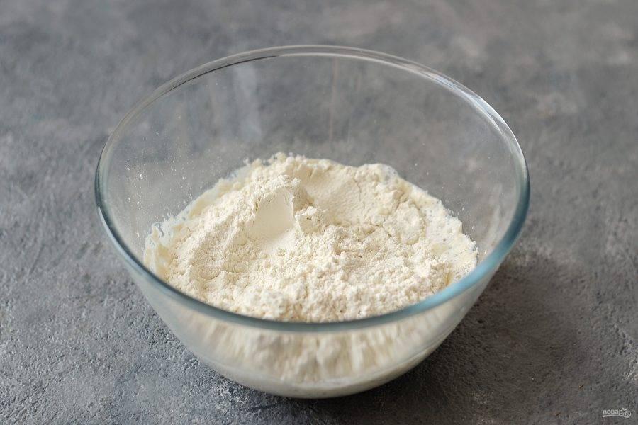 Просейте в миску муку и соль. Начните постепенно замешивать тесто.