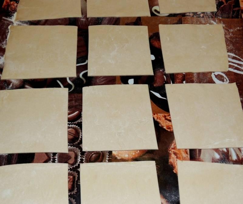 2. Тесто нужно выложить на присыпанную мукой поверхность и немного раскатать. Нарезать средними квадратиками.