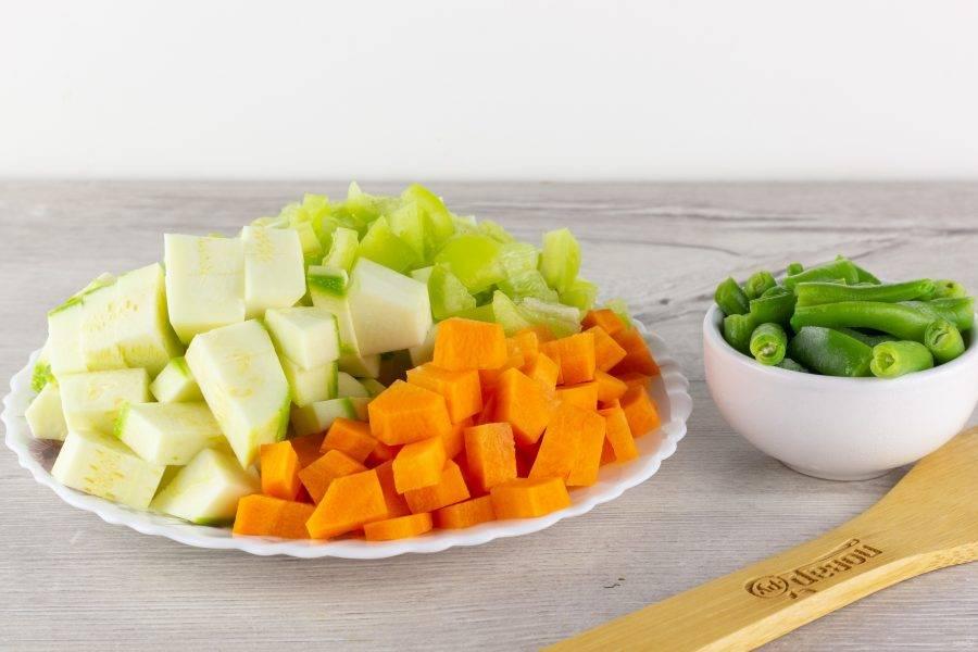 Морковь, кабачок и болгарский перец нарежьте кубиками. Фасоль также нарежьте небольшими кусочками.