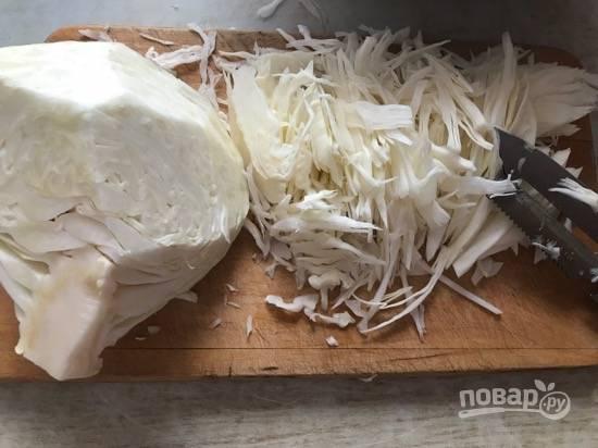 1. Белокочанную капусту мелко порубите, выложите в миску и помните руками.