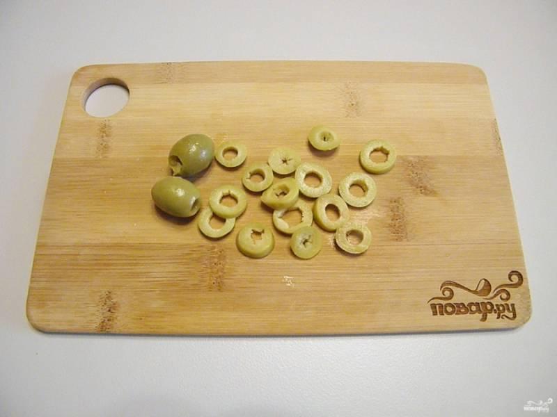 Оливки без косточек порежьте колечками. Зеленые оливки можно заменить на черные, с ними салат не менее вкусный получится.