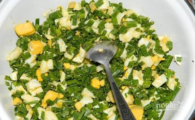 Теперь вам необходимо приготовить начинку. Для этого отварите оставшиеся шесть яиц вкрутую и очистите их от скорлупы. Нарежьте яйца мелкими кусочками. Вымойте зеленый лук, обсушите, нарубите и соедините с яйцами. Присолите и перемешайте.