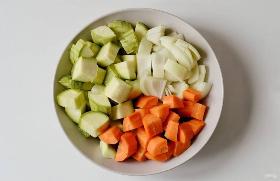 Кабачки нарежьте ломтиками. Старые кабачки очистите от жесткой кожицы и крупных семян. Морковь очистите от кожуры, нарежьте крупными ломтиками. Аналогично поступите с луком.