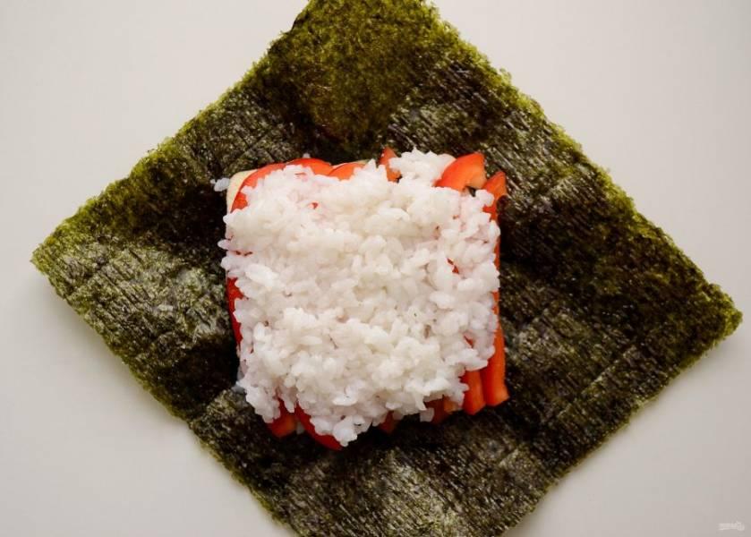 Сверху последним слоем положите еще одну ложку риса. Хорошенько разровняйте его.