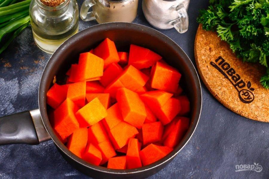 Тыкву нарежьте крупными кубиками и добавьте в емкость к луку, обжарьте примерно 1 минуту.