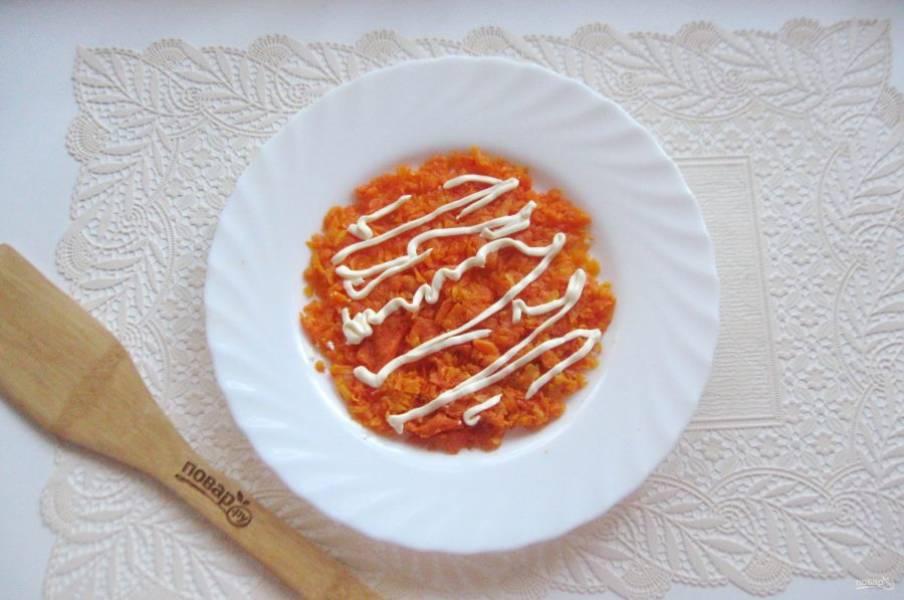 Морковь сварите, охладите и очистите. Натрите на терке и выложите первым слоем салата. Нанесите майонез на морковь.