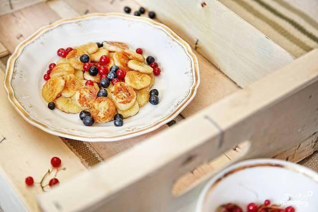 Жареные бананы переложить в тарелочку и посыпать ягодами.