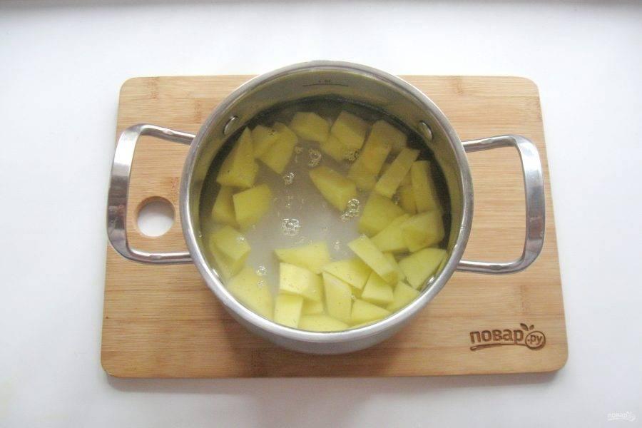 Картофель очистите, помойте и нарежьте. Выложите в кастрюлю, залейте водой и поставьте на плиту. Начинайте варить суп.