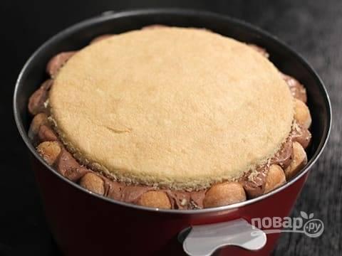Сверху накройте бисквитным коржом. Накройте пленкой и отправьте в холодильник на 6-8 часов.