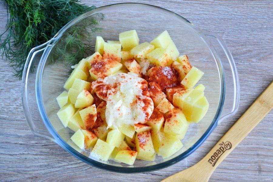 Картофель сложите в форму для запекания, к нему добавьте майонез, соль, перец и паприку.