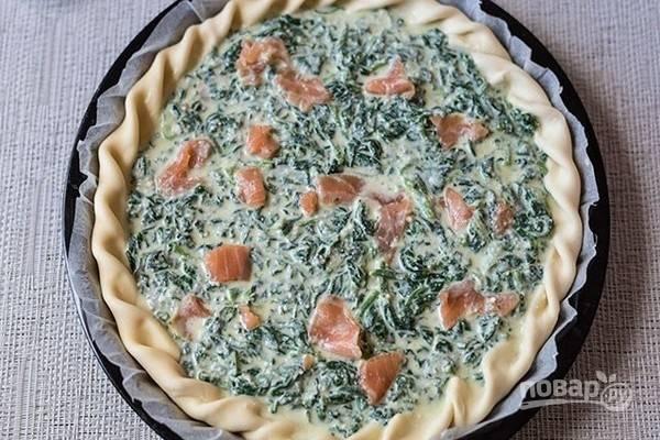 5.Смесь со шпинатом выложите на рыбу, разровняйте, добавьте сверху еще кусочки семги и разложите кусочки сливочного масла.