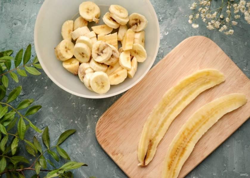 Разрежьте один банан вдоль, а потом ещё раз на половинку. Отложите их для украшения кекса. Оставшиеся бананы порежьте кружочками.