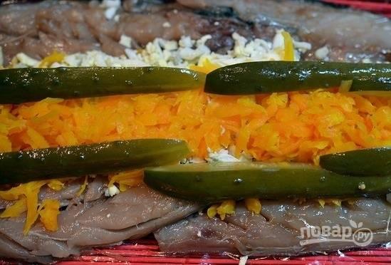 3. Выложите филе ровно, накладывая одну рыбку на другую немного. Посыпьте желатином. Выложите сверху тертую морковь, яйцо и нарезанный тонкими полосочками огурчик.