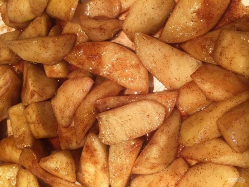 1.Яблоки вымойте и разрежьте пополам, удалите семена и срежьте кожуру. Нарежьте яблоки дольками. В сковороде разогрейте сливочное масло, выложите яблоки, добавьте к ним корицу, сахар (оставьте 1 ложку), обжаривайте 5-7 минут.