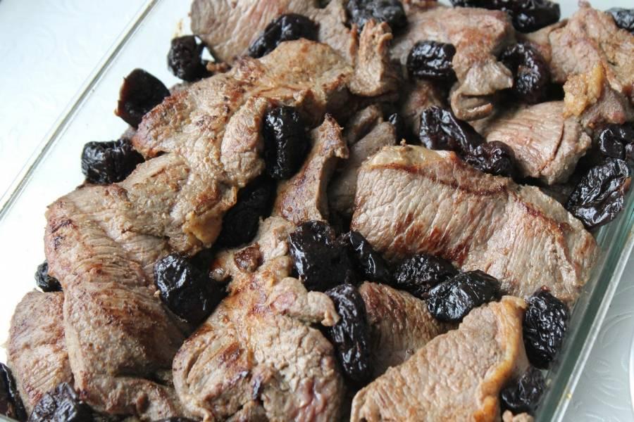 Затем мясо поместим в блюдо для запекания, равномерно разложив предварительно замоченный чернослив.