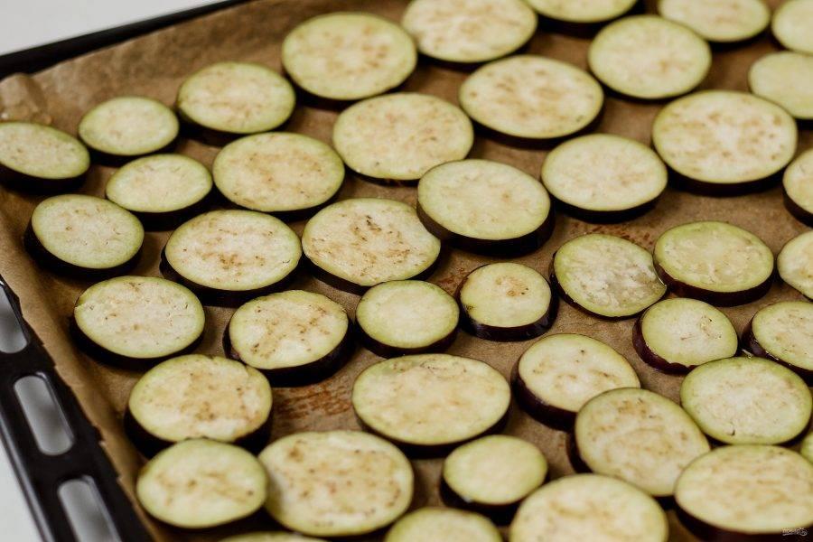 Баклажаны помойте, отрежьте хвостики, нарежьте кружочками толщиной 0,5 сантиметров. Выложите баклажаны на противень, смажьте растительным маслом. Выпекайте 25-30 минут в разогретой до 200 градусов духовке.