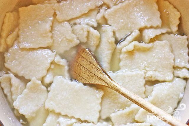 6. С помощью шпателя переместить клецки на густо посыпанную мукой тарелку. Пересыпьте слои клецок мукой. В большой кастрюле довести куриный бульон до кипения. Добавить клецки по одной за раз и аккуратно перемешать. Дополнительная мука на клецках поможет сгустить бульон.