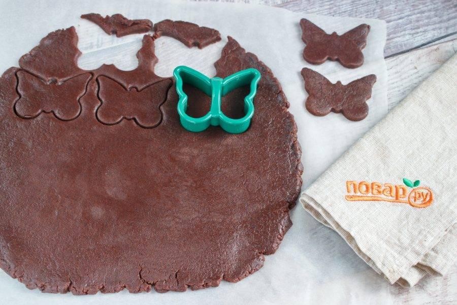 Разделите шоколадное тесто на 2-3 части. Раскатайте на пергаменте для выпечке в пласт, толщиной 5 мм, вырубите печенье.