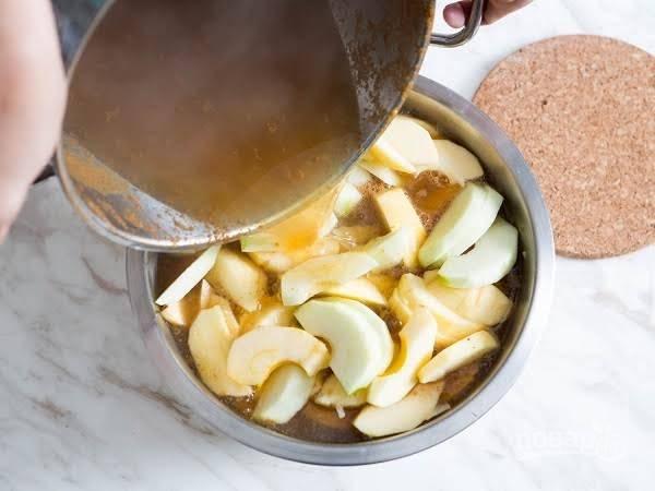 4. Очистите яблоки от кожицы и сердцевины. Нарежьте средними дольками и выложите в глубокую мисочку. Доведите до кипения яблочный сок и залейте им яблоки. Также в рецепт приготовления бабушкиного яблочного пирога можно использовать сидр.