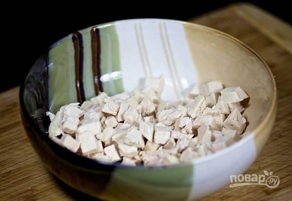 2. Готовую курочку остудите и нарежьте небольшими кубиками. Выложите её в салатник. Добавьте щепотку соли, можно также немного перца.