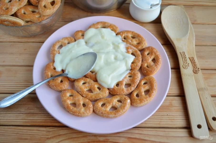 Возьмите большое блюдо для тортика. Выкладывайте печенье максимально плотно друг к другу. Смажьте его щедро кремом.