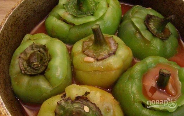 Перцы уложите в казанок так, чтобы их хвостики оказались сверху. Если расположите овощи вертикально, то начинка не будет выпадать в процессе приготовления. Разведите томатную пасту в стакане воды, залейте этим перцы. Тушите их на медленном огне полчаса с закрытой крышкой.