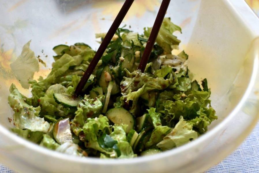 Полейте салат заправкой и легко перемешайте. Удобно это делать палочками, так овощи не мнутся.