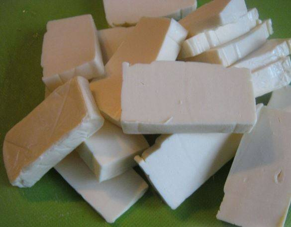 Плавленый сыр порежьте кусочками или потрите на терке.