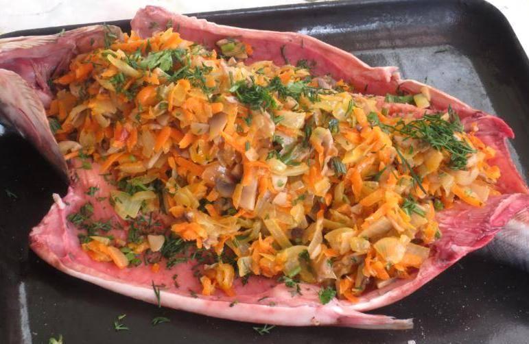 Теперь смешиваем обжаренные овощи и грибы, добавляем к ним соль и измельченную зелень, перемешиваем все. Когда начинка остынет, выкладываем ее внутрь горбуши и сшиваем ее брюшко нитками, делая большое расстояние между стежками.