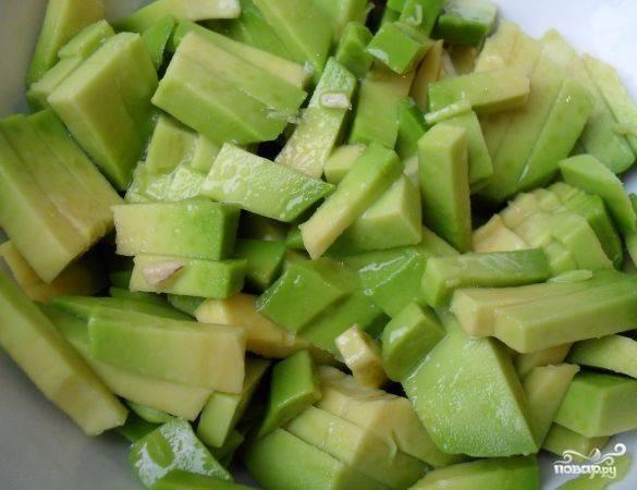 Авокадо нарежьте соломкой и сбрызните лимонным соком. Добавьте его в салат.