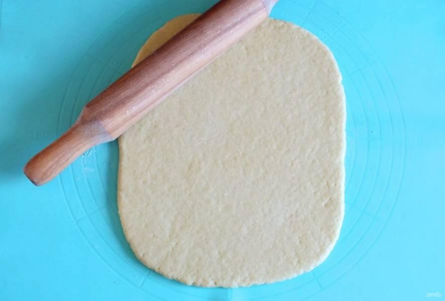 Рабочую поверхность припылите мукой. Выложите тесто. Раскатайте его в пласт толщиной 1 см.