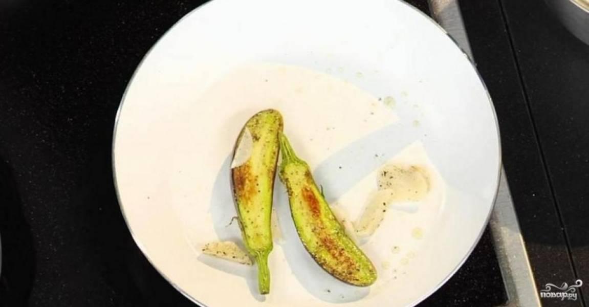 Баклажан помойте и разрежьте пополам. Чеснок очистите, измельчите, натрите им баклажан. Обжарьте оба овоща на оливквом масле минуты по 3 с каждой стороны.