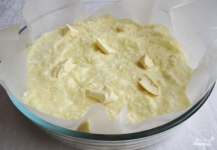 3.Аккуратно соединяем творожную массу со взбитыми белками, перемешиваем лопаткой сверху вниз. Форму для выпекания застилаем пергаментом и выкладываем тесто, сверху выкладываем нарезанные кусочки масла.