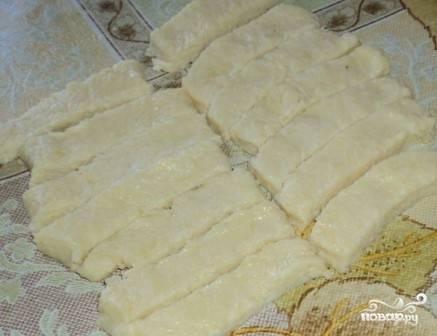 Смазываем стол или поверхность, на которой будем раскатывать тесто, растительным маслом. Раскатываем тесто в пласт толщиной 0,5 см и нарезаем на полоски шириной 1-1.5 см.