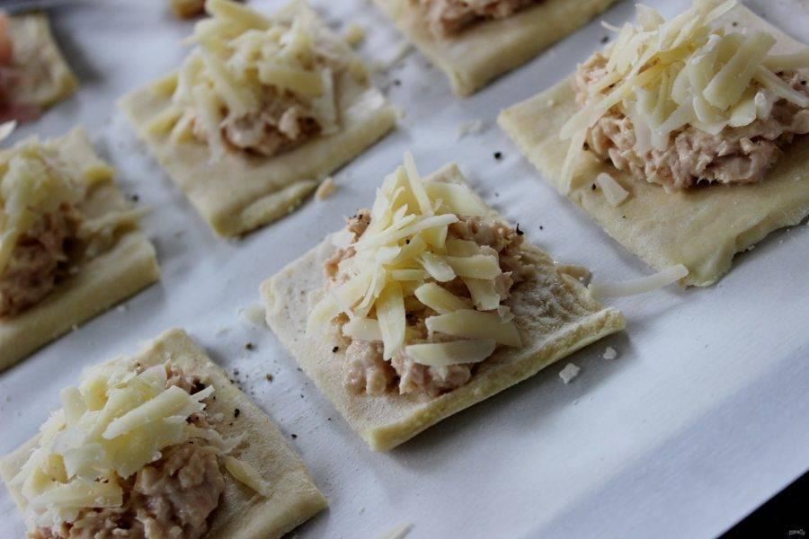 2.Слоеного тесто разделите на полоски, а затем еще на небольшие квадраты. Выложите по столовой ложке тунца по центру половины, а на вторую половину по центру налейте сливки с горчицей и выложите ветчину. Посыпьте все тарталетки твердым сыром, оставляя края.