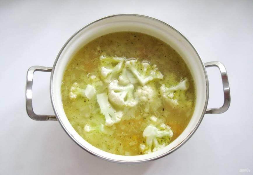 Сразу после хлопьев добавьте цветную капусту. Посолите суп по вкусу и варите еще 10 минут.