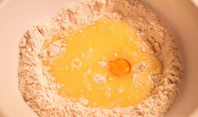"""2. В отдельной мисочке соединить 5 ложек молока, 1 столовую ложку сахара и дрожжи. Оставить на 5-7 минут, чтобы дрожжи начали """"работать"""". Молоко с маслом должно быть комнатной температуры, чтобы ввести в него дрожжи. Просеянную с солью муку всыпать в глубокую мисочку и сделать небольшое углубление посередине. Вбить яйцо."""