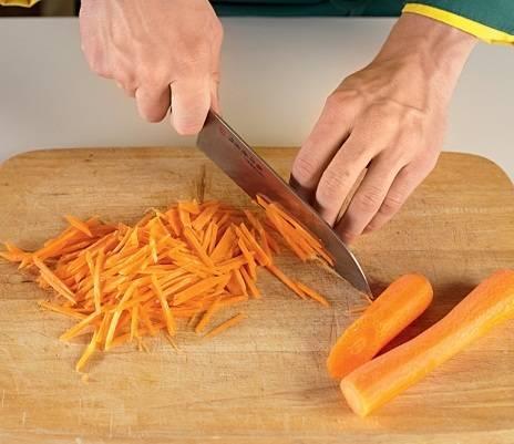 2. Очистите морковь. При помощи ножа нарежьте тонкими брусочками (можно и на терке натереть, но кусочками будет красивее). В рецепте приготовления маринованной капусты с клюквой используйте 1-3 моркови по вкусу.